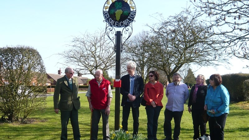 Several Parish notables at the unveiling of the refurbished Parish sign.