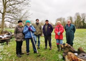 6 people working in the recreation ground renewing the woodland woodchip path