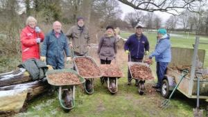 5 people with wheelbarrows full of woodchip to renew the woodland path