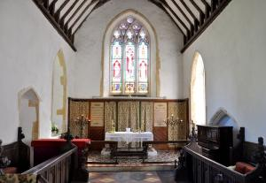 An interior picture of St Peter's Carlton showing the aisle, altar and stsained glass main window
